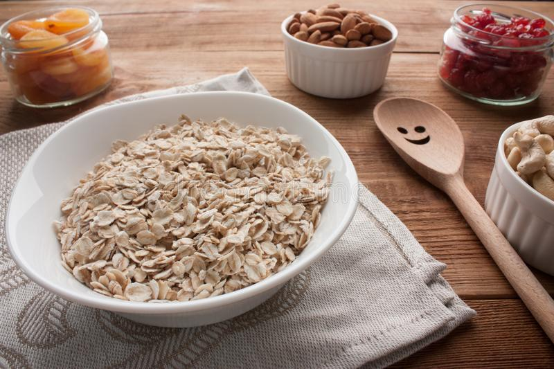 Oat flakes in bowl with dried apricots, dried cherries, almonds, cashews in jars on wooden table with wooden spoon. royalty free stock images