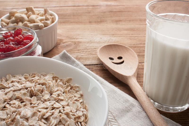 Oatmeal with dried cherries, cashews, milk and a wooden spoon on wooden table. stock photo