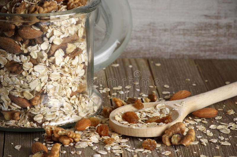 Oatmeal flakes with nuts. Dry oatmeal flakes with walnuts, almonds and raisins in glass jar and wooden spoon on rustic wooden background royalty free stock images