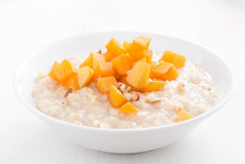 Oatmeal with fresh apricots and nuts on a white wooden table stock images