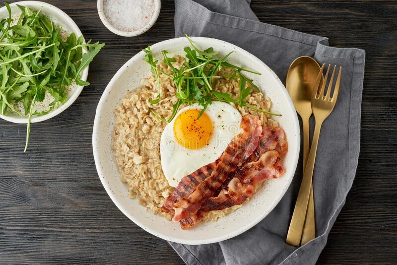 Oatmeal, fried egg and fried bacon. Balance of proteins, fats, carbohydrates. Close up. Oatmeal, fried egg and fried bacon. Brutal man sport breakfast. Hearty stock image
