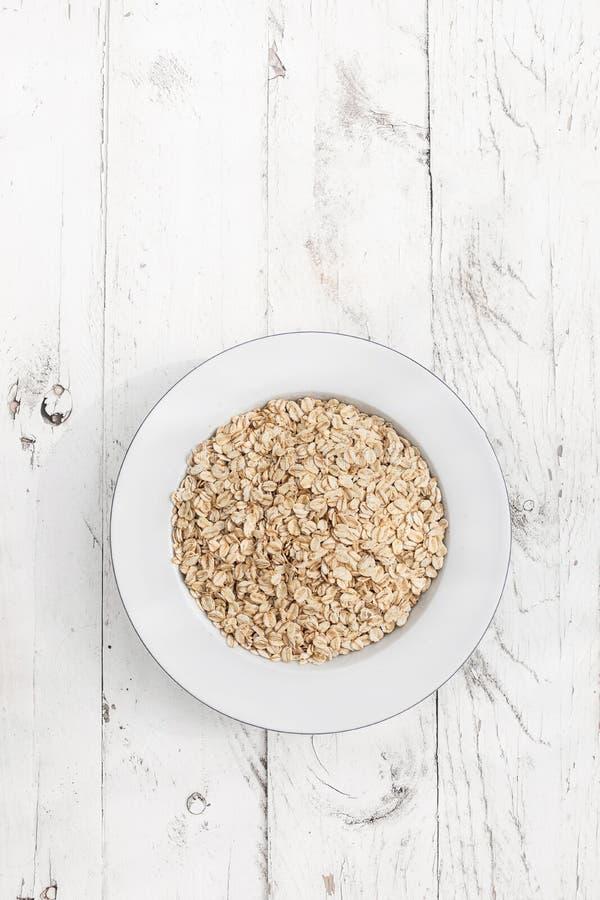 oatmeal I fiocchi di avena si sfaldano su fondo di legno bianco immagine stock