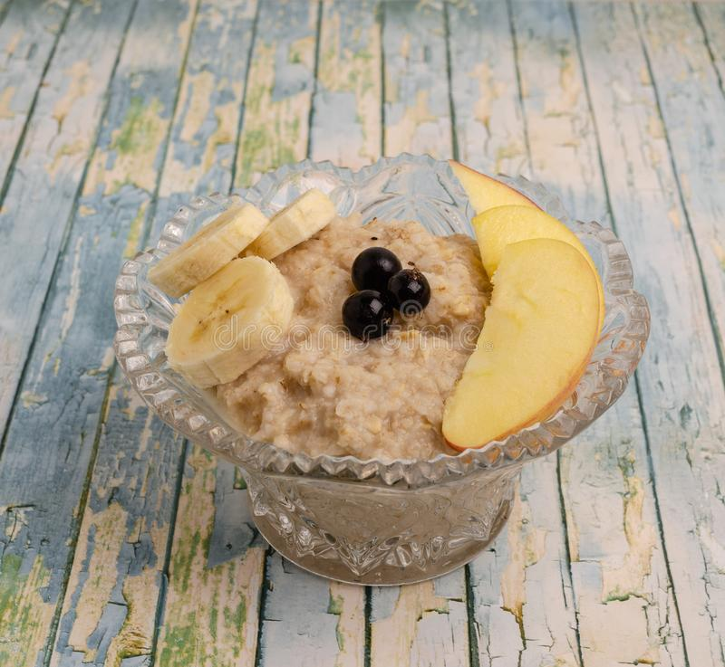 Oatmeal in a blue plate, milk, dried fruits royalty free stock image