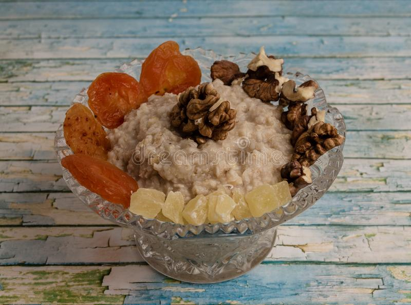 Oatmeal in a blue plate, milk, dried fruits royalty free stock images