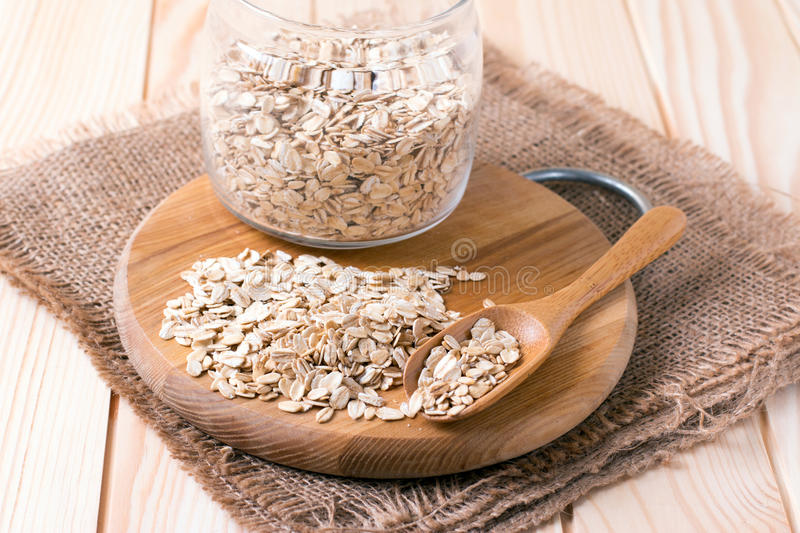 Oatmeal or oat flakes in bowl and scoop on dark wooden table royalty free stock photography