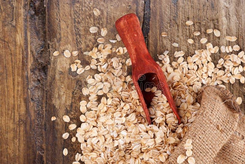 Oatmeal płatki w burlap grabiją z łyżką na brown drewnianym stole, zdjęcia royalty free