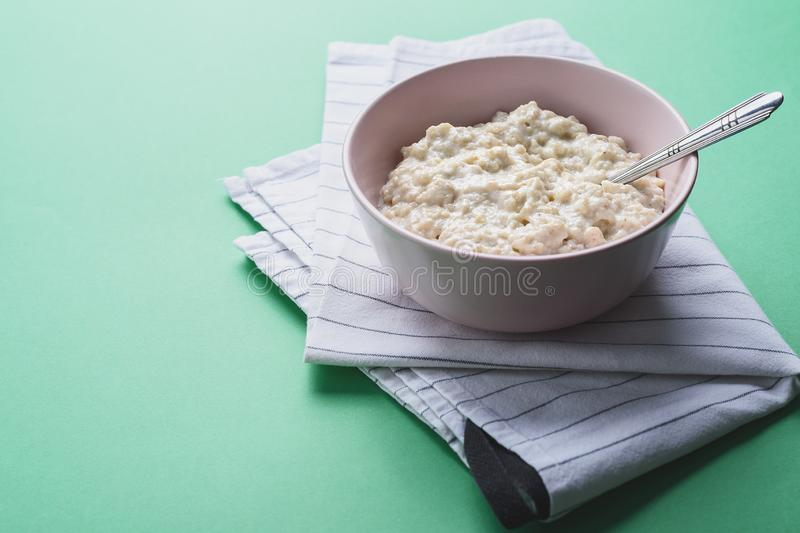 Oatmeal in a pink plate with a spoon on a white cloth, green background.  stock photos