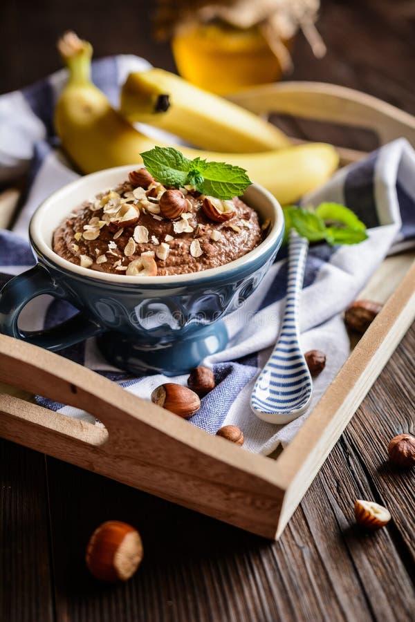 Oatmeal porridge with banana, hazelnut, chocolate and honey stock photo