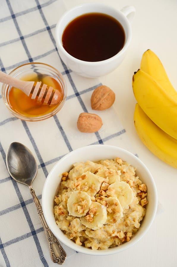 Oatmeal porridge with banana, honey and walnuts royalty free stock image