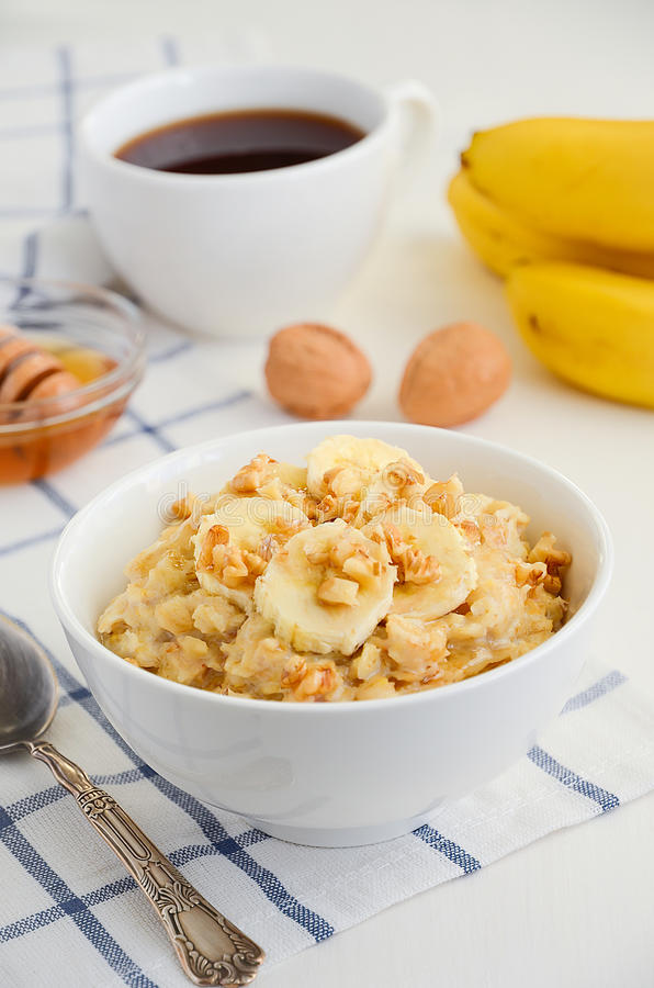 Oatmeal porridge with banana, honey and walnuts royalty free stock photo