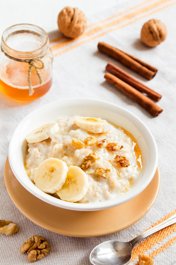 Oatmeal porridge with banana, nuts and honey stock photography