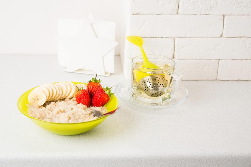 Oatmeal porridge with banana and strawberry in green bowl with hot tea royalty free stock photo