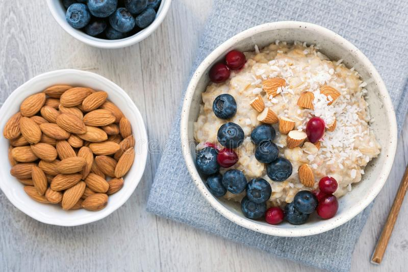 Oatmeal porridge with berry and nuts in white bowl. Table top view stock images