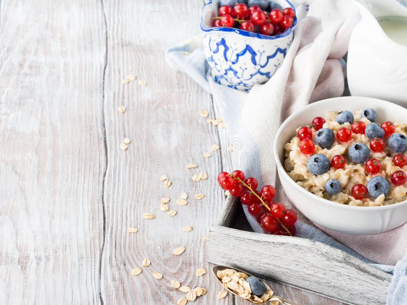 Oatmeal porridge with blueberries and red currants on rustic woo. Breakfast with bowl of oatmeal porridge with blueberries and red currants on a kitchen napkin stock images