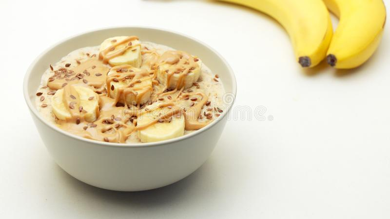 Oatmeal Porridge Bowl with Banana and Nut Butter. stock photo