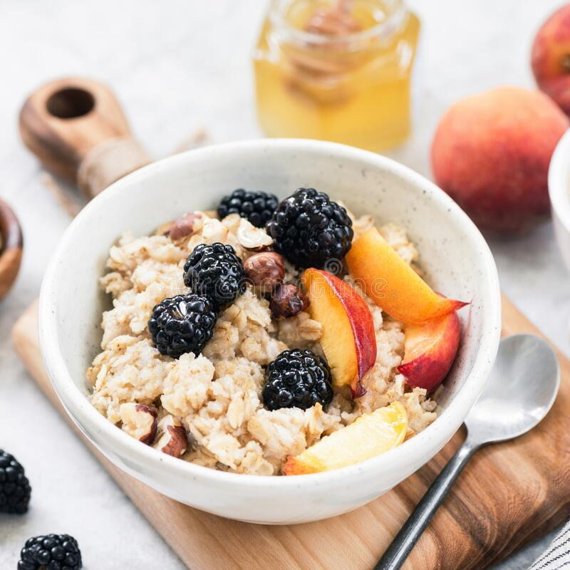 Oatmeal porridge bowl with fruits, berries royalty free stock photography