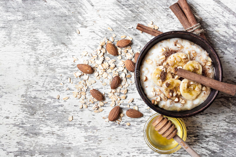 Oatmeal porridge in ceramic bowl. healthy breakfast. Oatmeal porridge in ceramic bowl with banana, nuts, honey and cinnamon on rustic wooden background. healthy stock photo