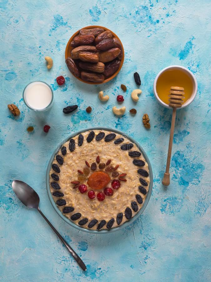 Oatmeal porridge with dried fruits on a blue table. royalty free stock photography