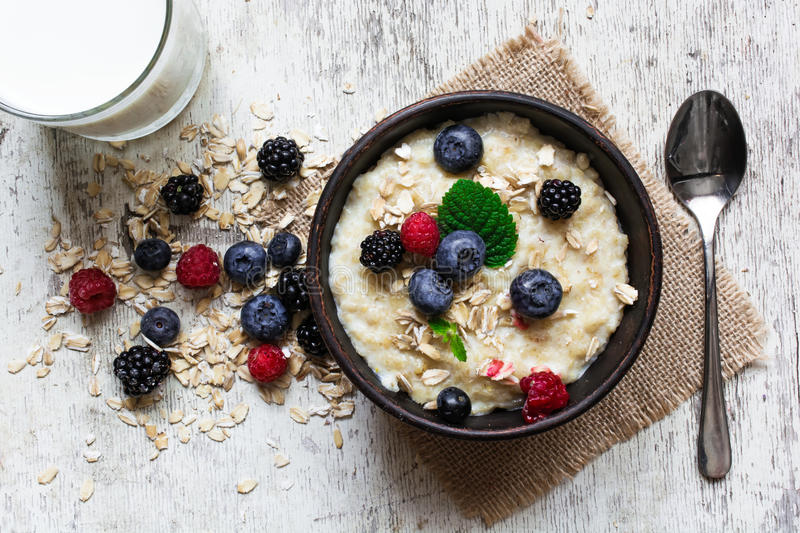 Oatmeal porridge with fresh berries, glass of milk and spoon royalty free stock image