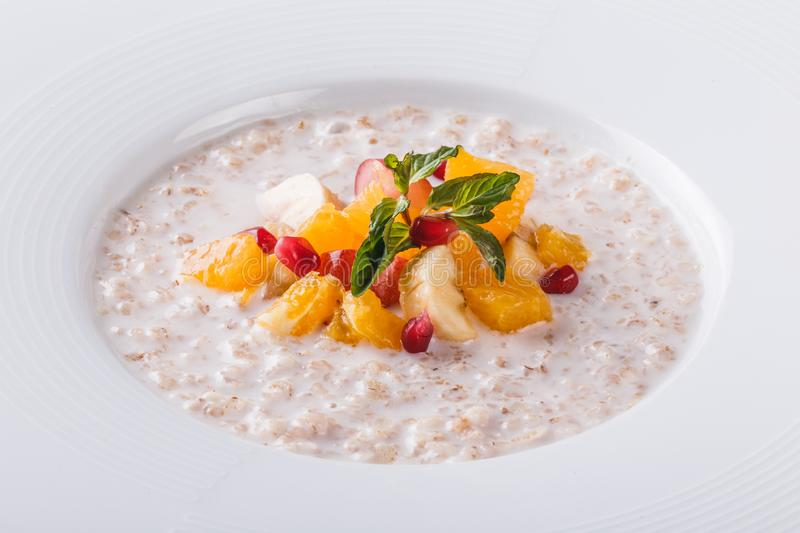 Oatmeal porridge with fresh fruit and mint in plate over grey background. Healthy breakfast ingredients. Clean eating, vegan food. Concept stock image