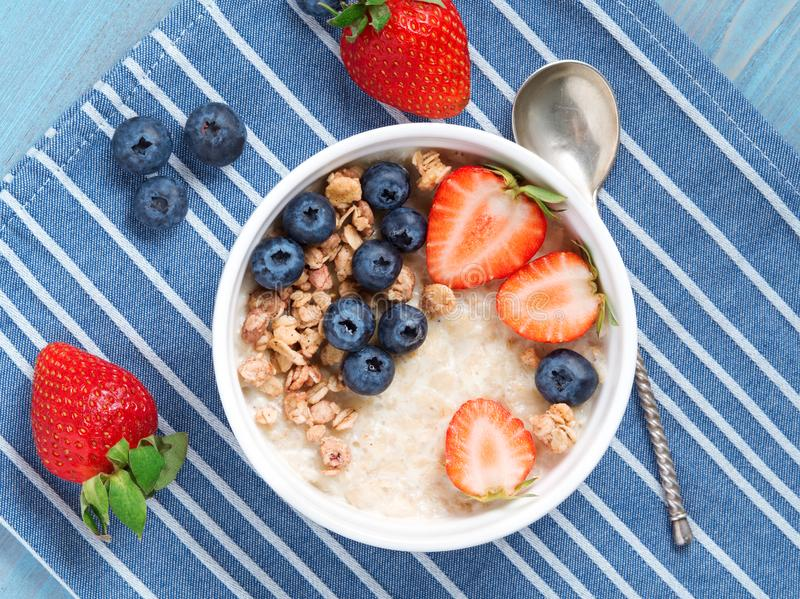 Oatmeal porridge with fresh strawberry, blueberry, granola on blue background. Healthy breakfast. Top view, close-up royalty free stock photo