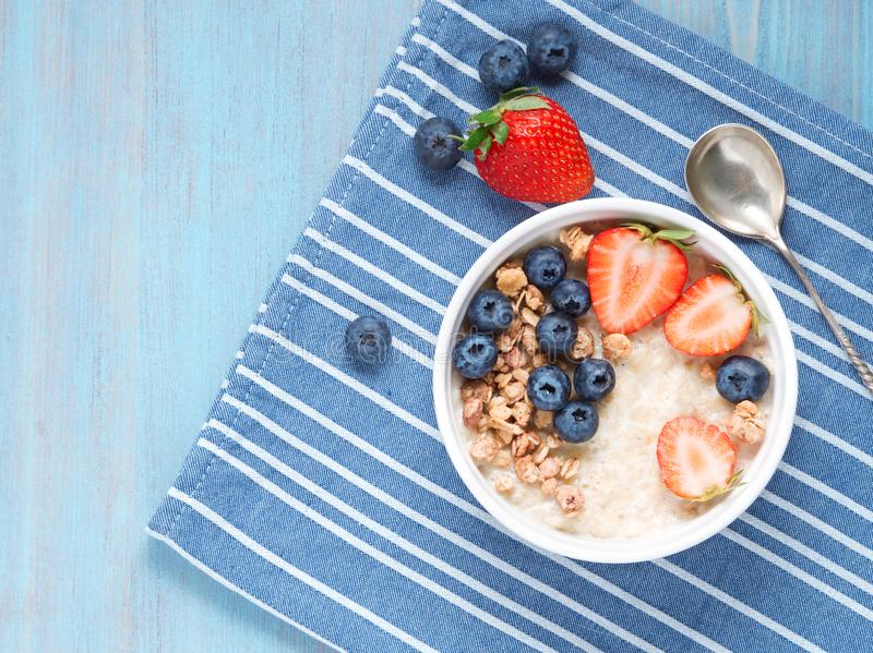 Oatmeal porridge with fresh strawberry, blueberry, granola on contrast blue background. Healthy breakfast. Top view. royalty free stock images