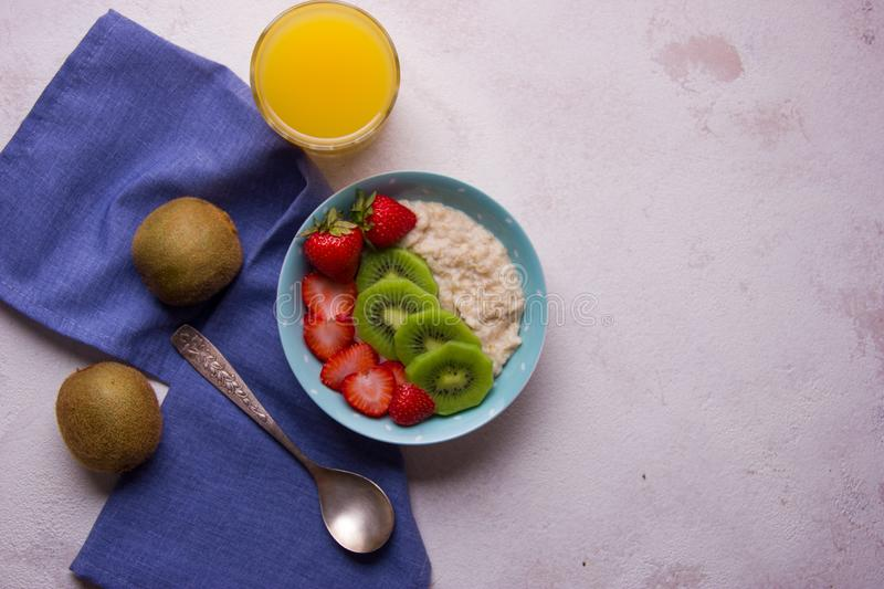Oatmeal porridge with strawberry and kiwi in bowl on background royalty free stock photo