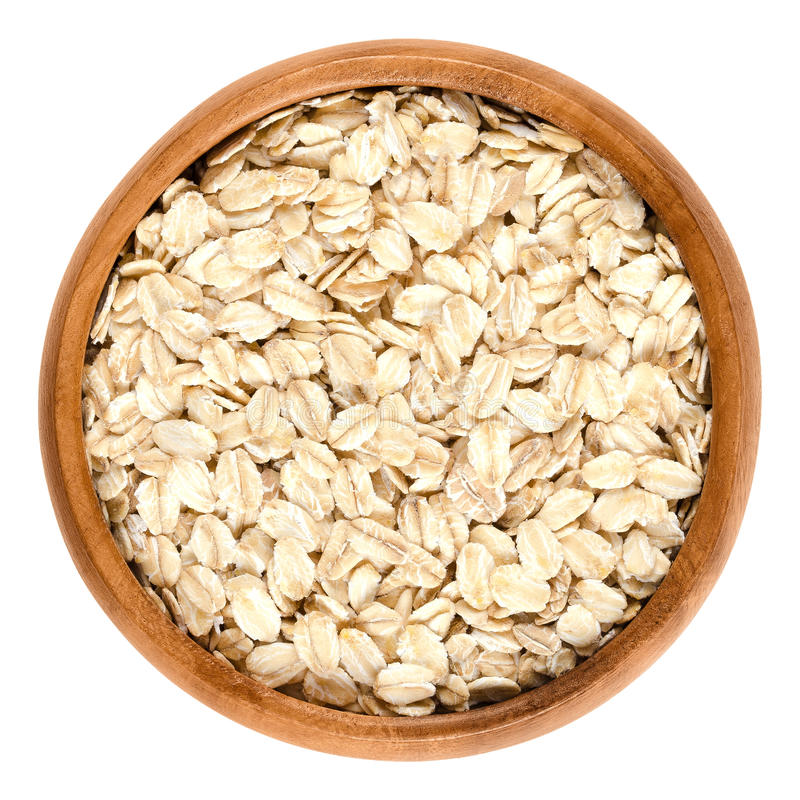 Oatmeal, rolled oats in wooden bowl over white royalty free stock photography
