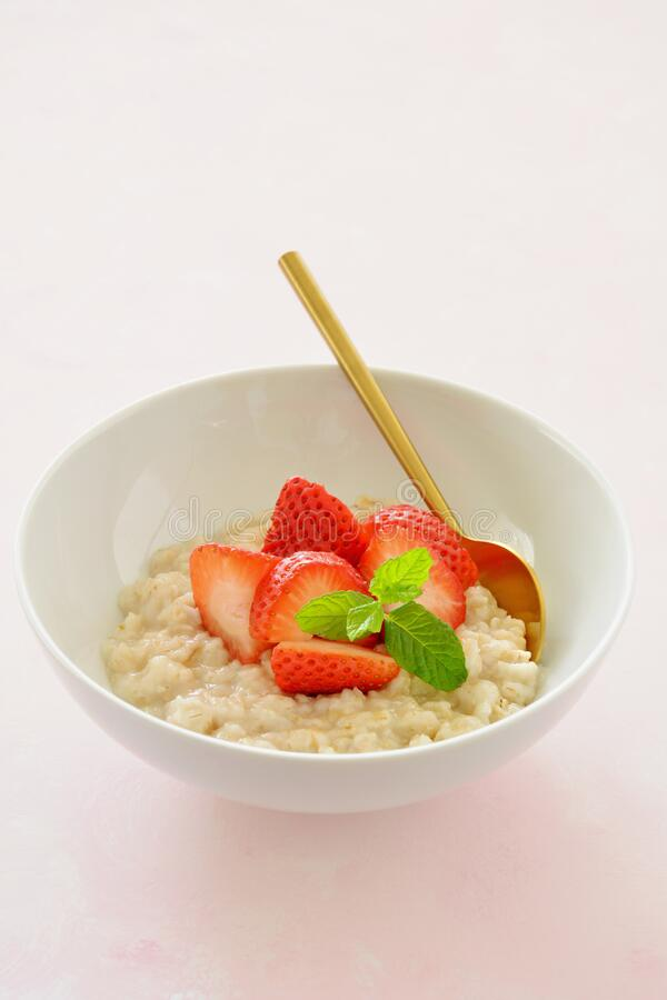 Oatmeal with organic strawberries royalty free stock photo