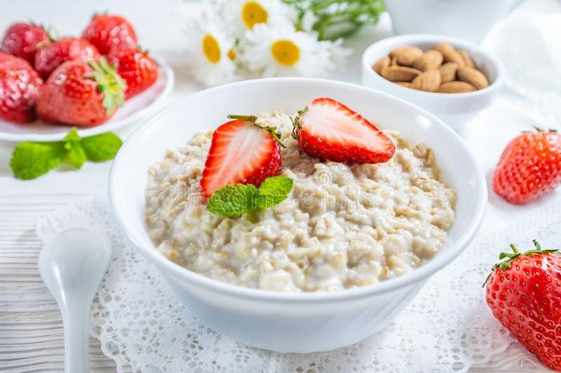 Oatmeal with strawberry and nuts in bowl on white wooden table royalty free stock photos