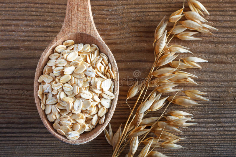 Oatmeal on wooden spoon stock photography