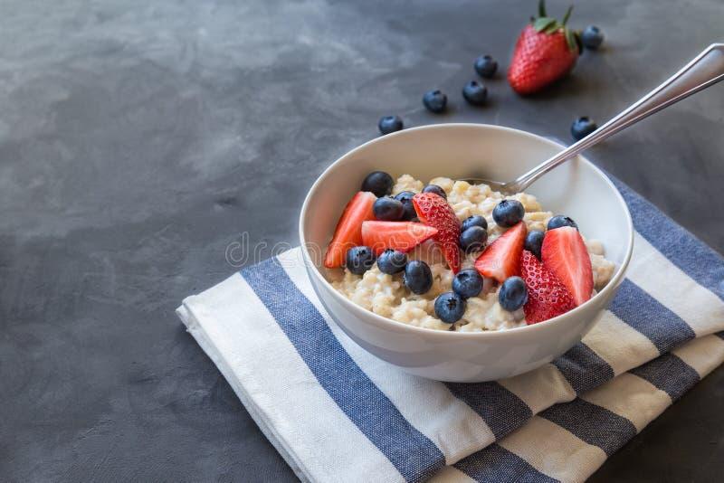 Oatmeal z czarnymi jagodami i truskawkami dla śniadania zdjęcie royalty free