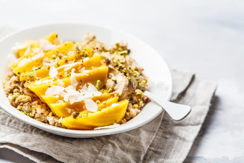 Oatmeal z mango, koksem, masłem orzechowym i dokrętkami w białym talerzu, Weganinu jedzenie, zdrowy śniadanie, roślina opierał si obrazy royalty free