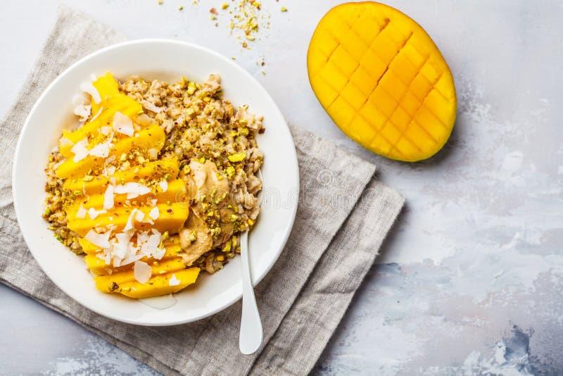 Oatmeal z mango, koksem, masłem orzechowym i dokrętkami w białym talerzu, Weganinu jedzenie, zdrowy śniadanie, roślina opierał si fotografia royalty free