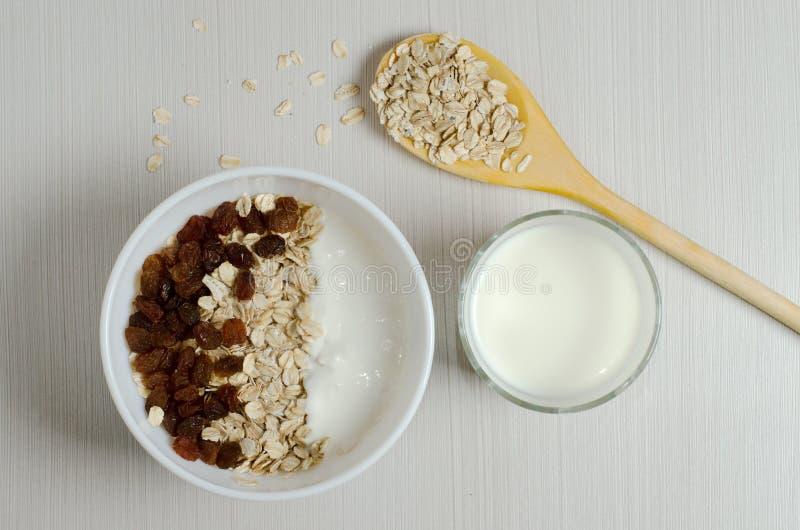Oatmeal z rodzynkami i jogurtem Oatmeal w drewnianej łyżce, mi obrazy stock