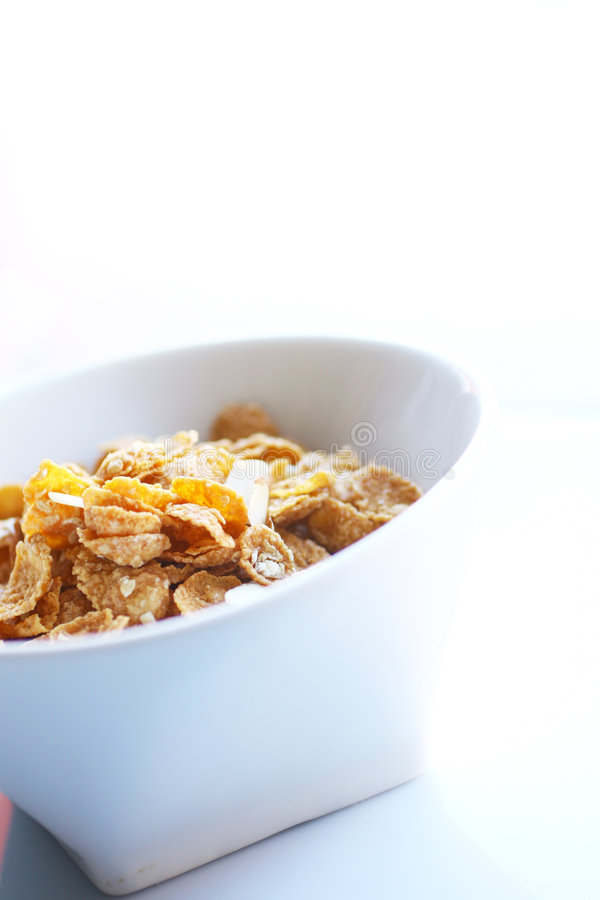 Oats and almond cereal. White bowl with oats and almond cereal on a white background stock image