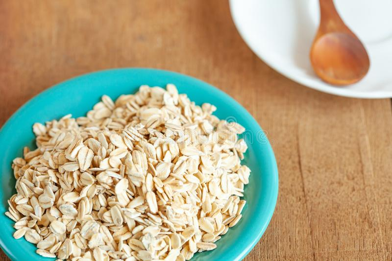 Oats flakes in dish on wood. Table royalty free stock photography