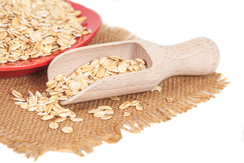 Oats flakes pile in wood spoon on white. Background stock images