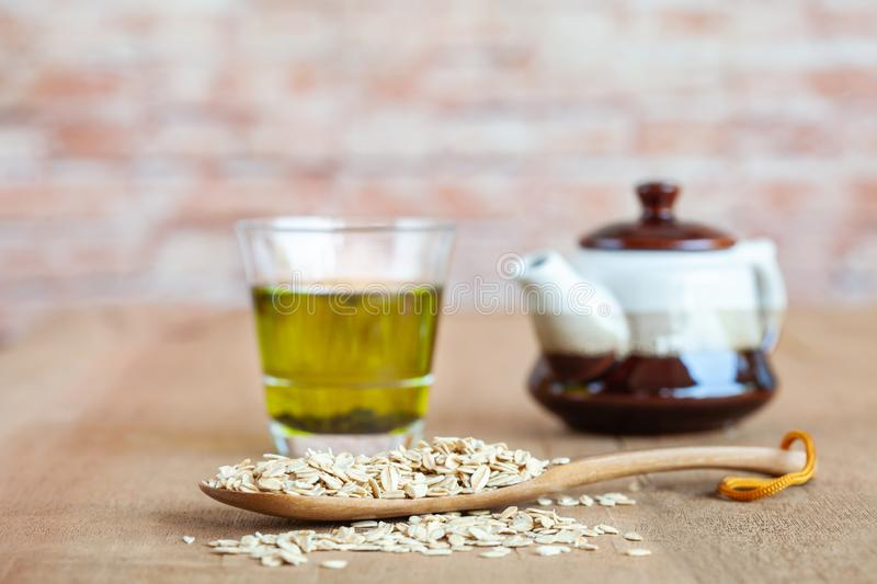 Oats flakes in wood spoon with hot green tea. On wood table stock photos