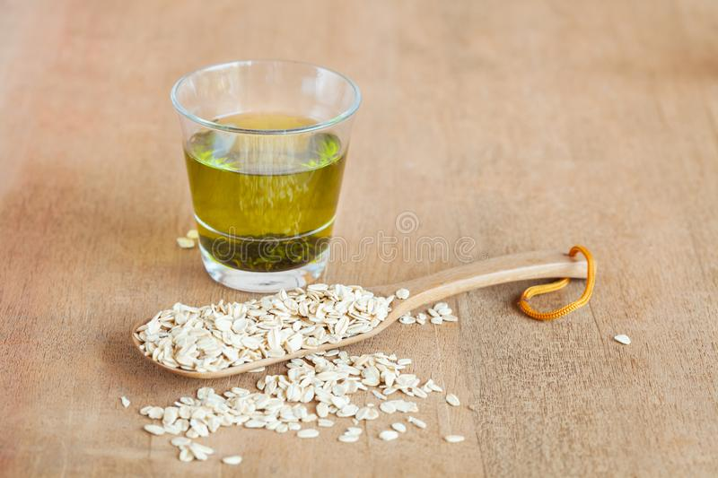 Oats flakes in wood spoon with hot green tea. On wood table stock photo