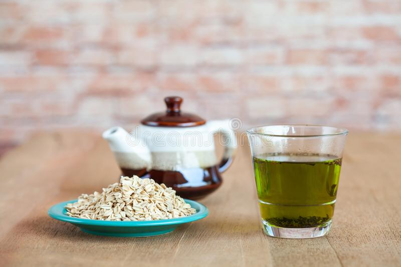 Oats flakes in wood spoon with hot green tea. On wood table royalty free stock image