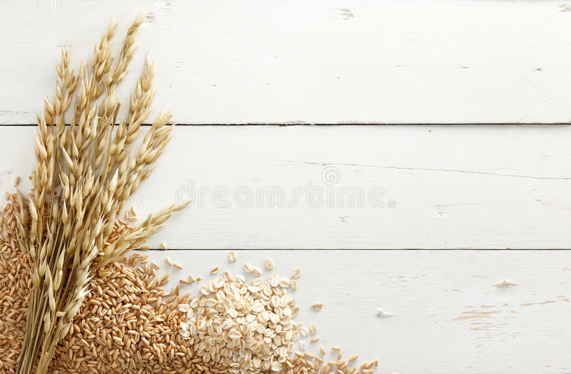 Oats with grains. Oats with its processed and unprocessed grains against white wood background royalty free stock photography