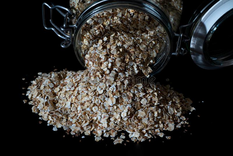 Oats poured out from a glas jar royalty free stock image