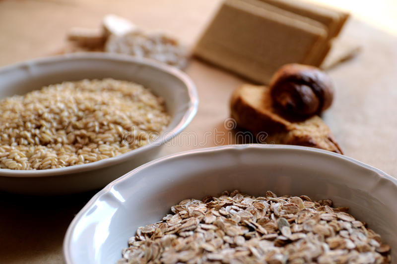 Oats and rice in a bowl. Rice cakes and bread in background. Foods high in carbohydrate. stock photography