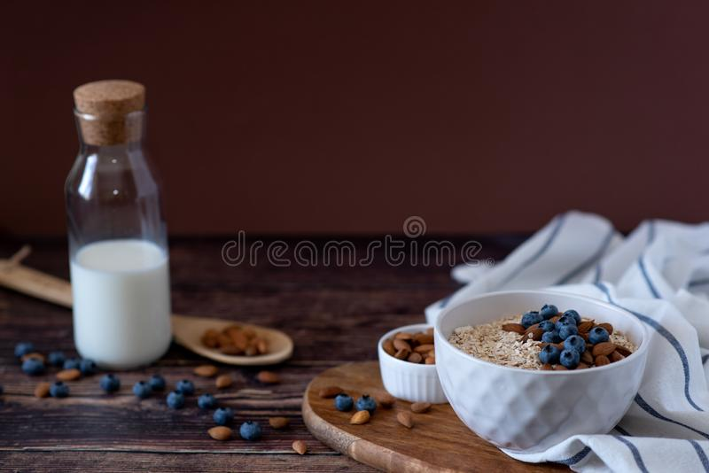 Oats in a spoon in a plate on a table scattered oat flakes stock photography
