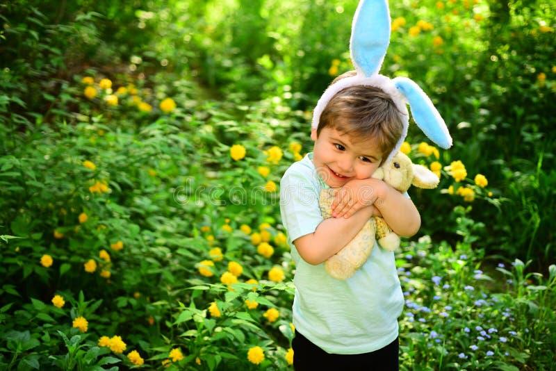 Oavbrutet tjata ungen med kaninöron Hareleksak Äggjakt på vårferie Förälskelsepåsk Isolerat på vit bakgrund Pysbarn i gräsplan royaltyfri fotografi