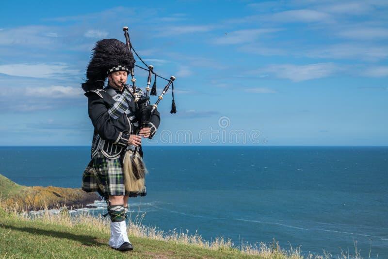 Oavkortad klänningkod för traditionell skotsk säckpipeblåsare på havet royaltyfria bilder
