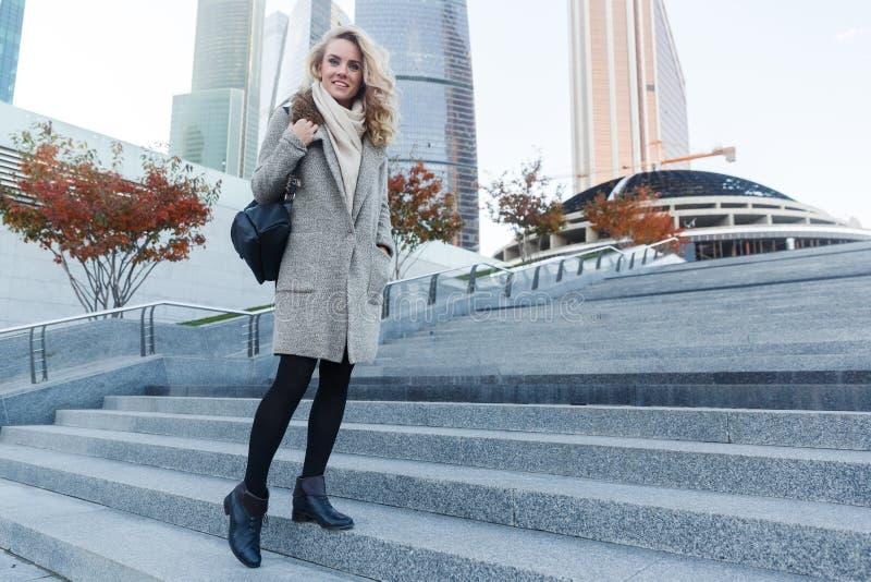 Oavkortad längd för stående av den unga kvinnan på stege utomhus fotografering för bildbyråer