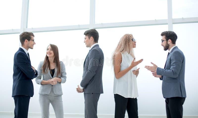 Oavkortad tillväxt en grupp av affärsfolk som talar i lobbyen av kontoret royaltyfri fotografi