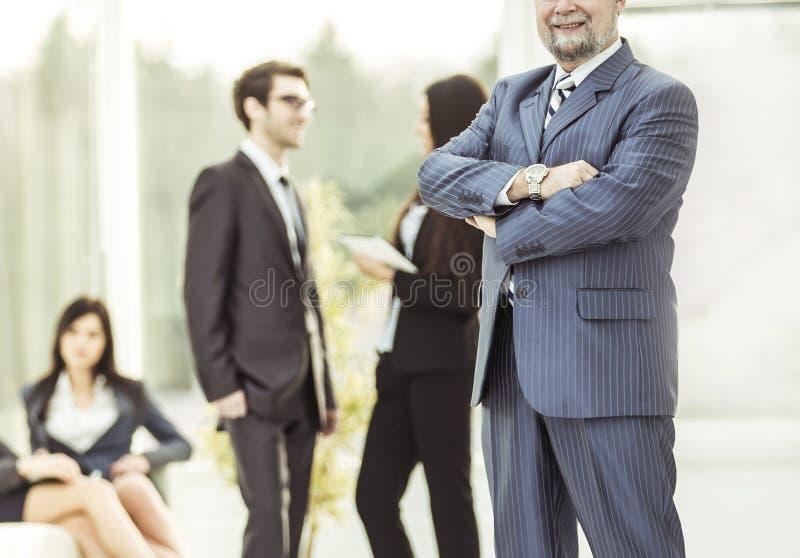 Oavkortad tillväxt för foto - en lyckad affärsman på bakgrunden av affärslaget i det rymliga kontoret arkivbild